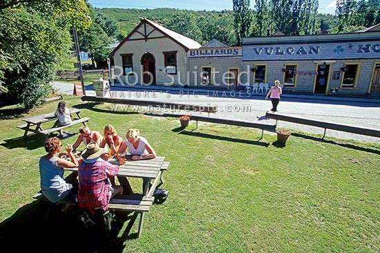 A beer in the sun in front of the Historic Vulcan Hotel (c.1869), St Bathans, Central Otago District, Otago Region, New Zealand (NZ) stock photo.