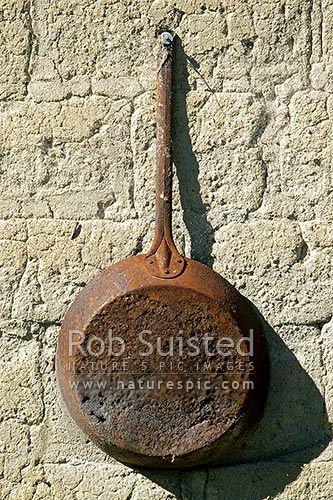 Old frying pan hanging on old stone cottage, St Bathans, Central Otago District, Otago Region, New Zealand (NZ) stock photo.