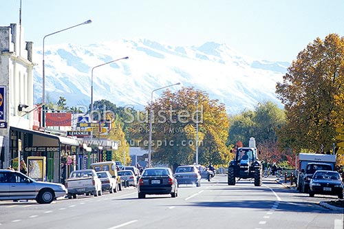 Main street of Fairlie, with the snow covered Two Thumb Range behind. Tractor on road, Fairlie, MacKenzie District, Canterbury Region, New Zealand (NZ) stock photo.