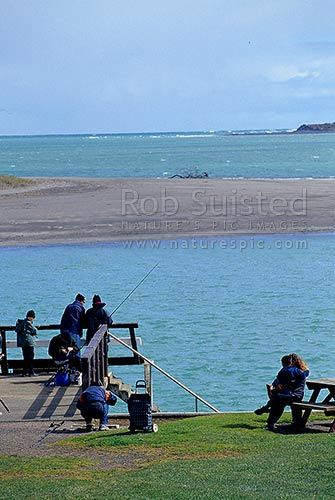 Sea fishing on jetty at Kopua Beach, Raglan, Waikato District, Waikato Region, New Zealand (NZ) stock photo.
