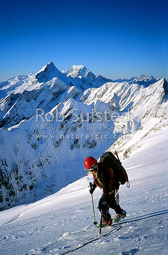 Mountaineer descending from Vampire Peak (2654m). Mount (Mt) Sefton and Mount (Mt) Cook behind.. PHOTO BY: Phil Suisted, Aoraki / Mount Cook National Park, MacKenzie District, Canterbury Region, New Zealand (NZ) stock photo.