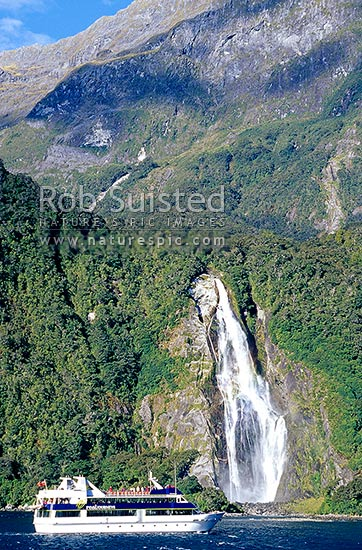 Real Journey's tour vessel in front of Bowen Falls (162m high), Milford Sound, Fiordland National Park, Southland District, Southland Region, New Zealand (NZ) stock photo.