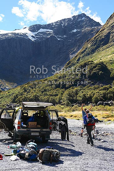 Trampers arriving at road end after a hike in Fiordland to Gertrude Saddle. Backpackers, trampers, hikers, Fiordland National Park, Southland District, Southland Region, New Zealand (NZ) stock photo.