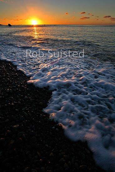 A calm sea at sunset over Pukerua Bay beach, Pukerua Bay, Porirua City District, Wellington Region, New Zealand (NZ) stock photo.