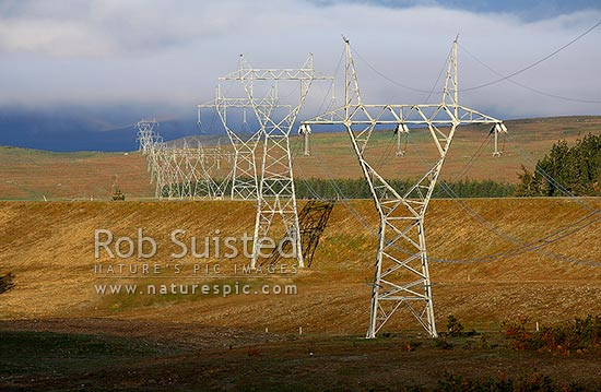 Power Pylons transmitting electricity across farmland in the MacKenzie Basin, MacKenzie Basin, MacKenzie District, Canterbury Region, New Zealand (NZ) stock photo.