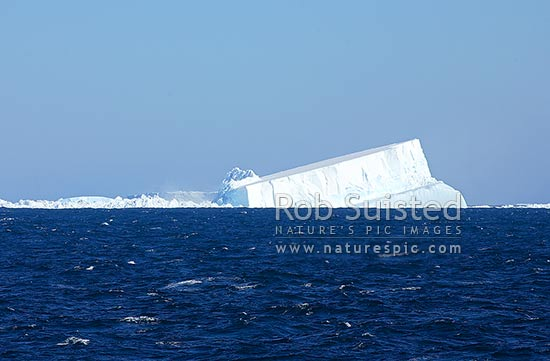 Giant Tabular Iceberg destructing. As berg crumbles into brash and bergy bits at left it rotates and bobs. Est. 1km long. Image 3 in series of 7, Terre Adelie Land, Antarctica stock photo.