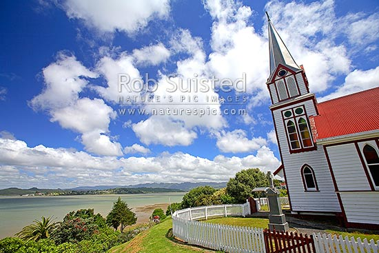 The Catholic Church of Our Lady of the Assumption, historic Gothic style church built at Motukaraka Point in 1910 overlooking Rawene and Hokianga. Tombstone in front of church, Motukaraka, Hokianga Harbour, Far North District, Northland Region, New Zealand (NZ) stock photo.