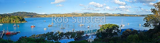 Panoramic view over Mangonui township on White Point, Mangonui wharf, and fishing vessels, boats and yachts moored in harbour, Mangonui, Far North District, Northland Region, New Zealand (NZ) stock photo.