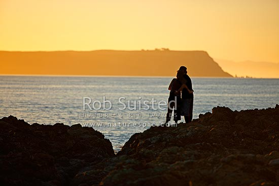 Young couple in love hugging during sunset on rocky shore at beach, Porirua City District, Wellington Region, New Zealand (NZ) stock photo.