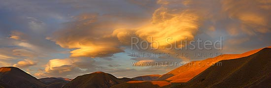 Lenticular clouds gathering in evening sunset over Lindis Pass and the Dunstan Range, signalling coming bad weather and winds. Panorama, Lindis Pass, MacKenzie District, Canterbury Region, New Zealand (NZ) stock photo.
